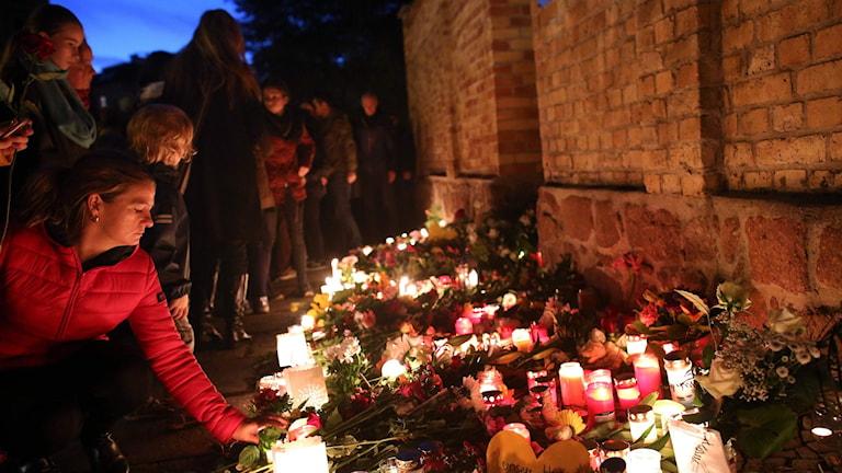 Flera personer lägger blommor vid tända ljus i Halle