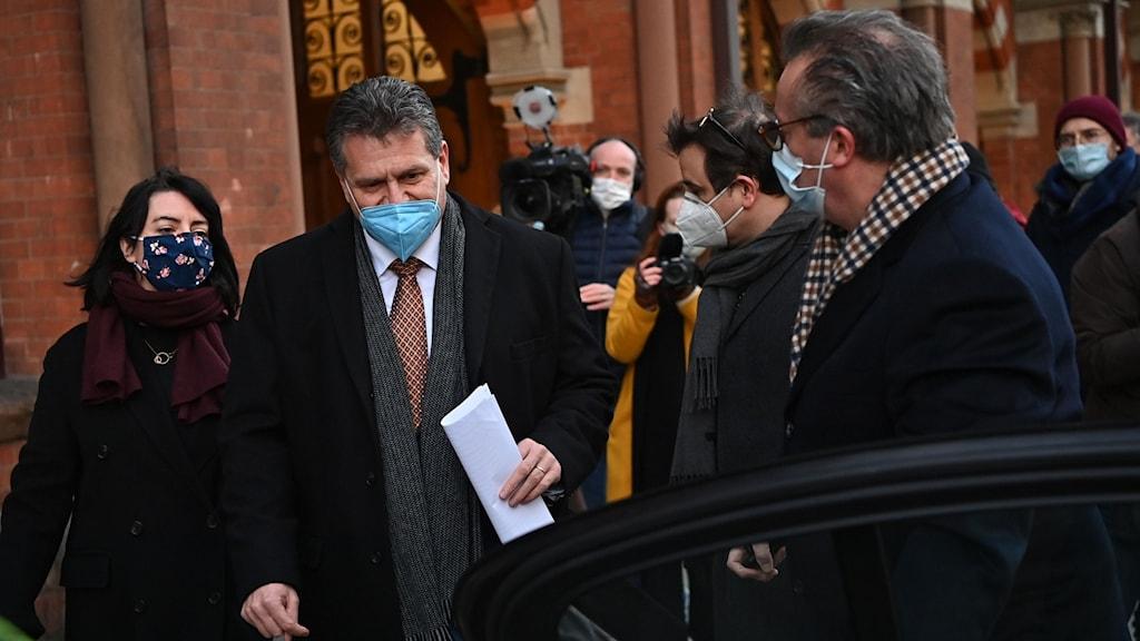 Kostymklädd man med blått munskydd omgiven av reportrar och fotografer.