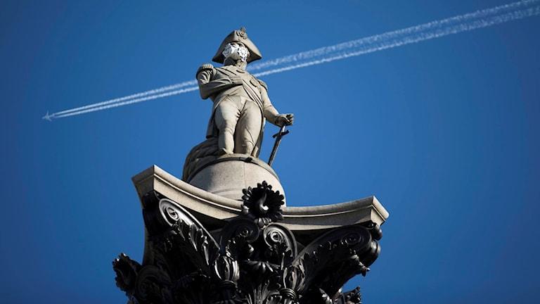 Miljöaktivister har satt en skyddsmask på Nelsonstatyn i London.