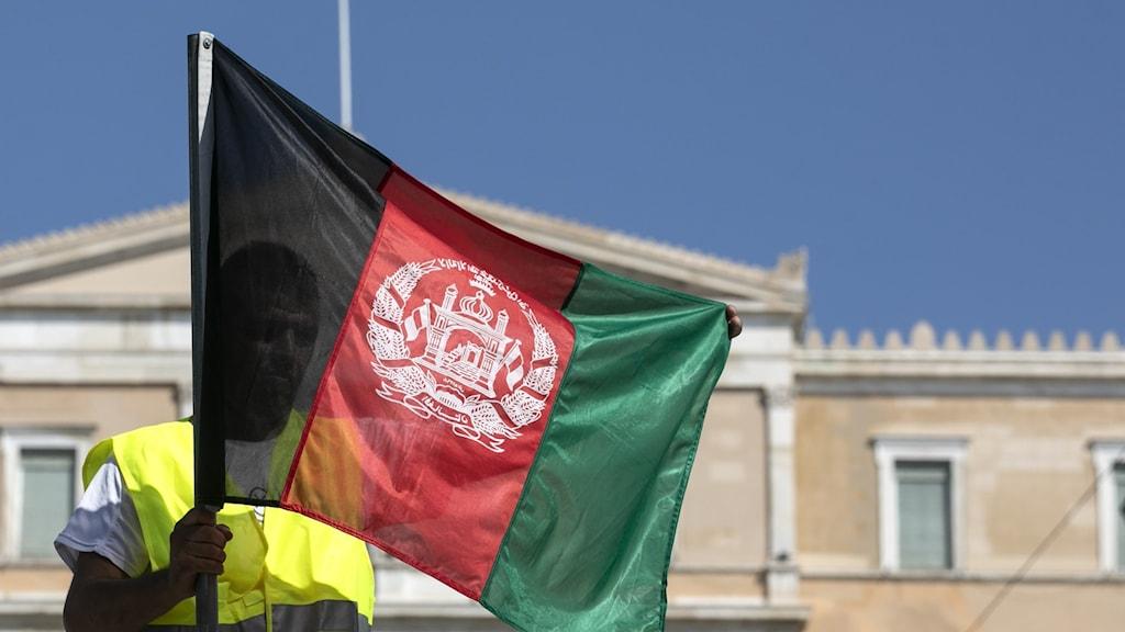 En demonstrant i Grekland håller en Afghansk flagga.