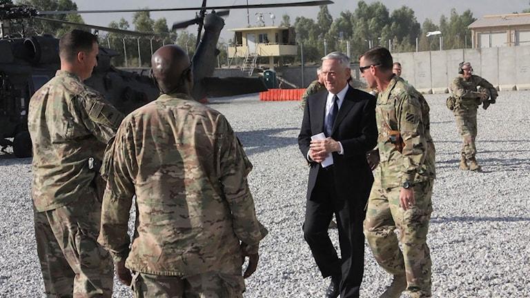 En man i kostym går med män i militäruniformer