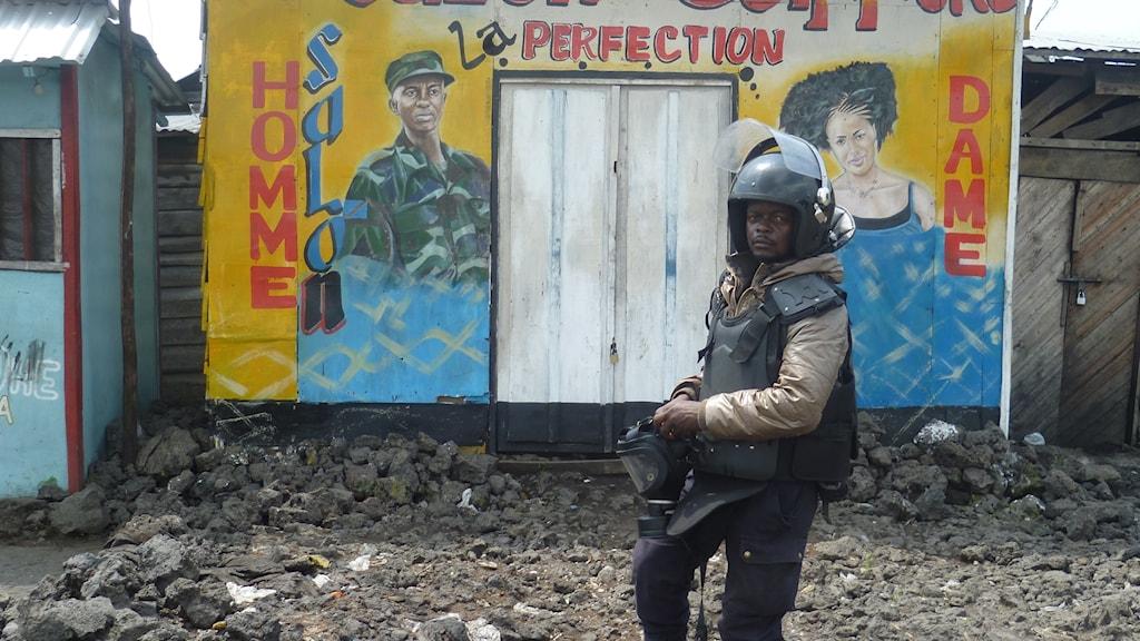 En polis i kravallutrustning tar fram gasmasken i Majengo i norra Goma.