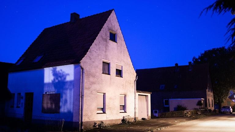Ett litet hus med grå putsfasad