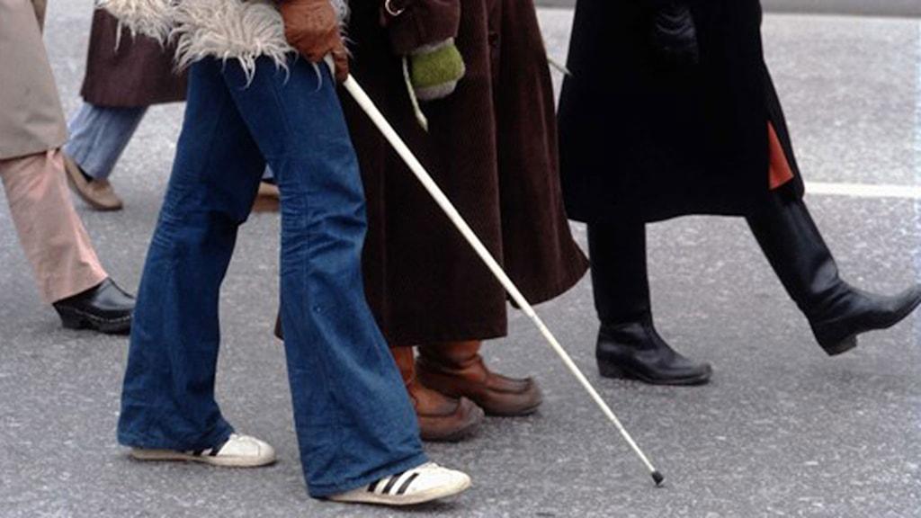 Person går med blindkäpp.