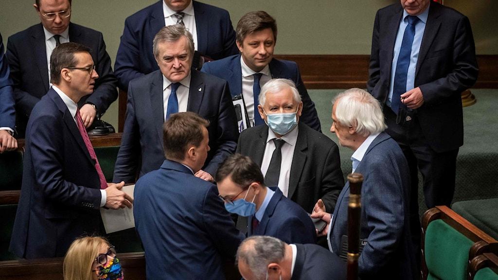 Lag och Rättvisas partiledare Jarosław Kaczyński i munskydd. Mateusz Morawiecki till höger.