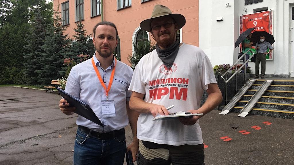 Två belarusiska män som övervakar presidentvalet står utanför en vallokal i Minsk.