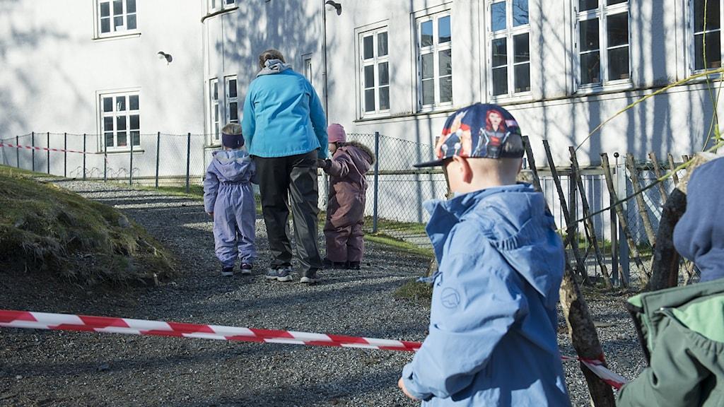 En kvinna lämnar barn på en förskola med avspärrningstejp utanför.