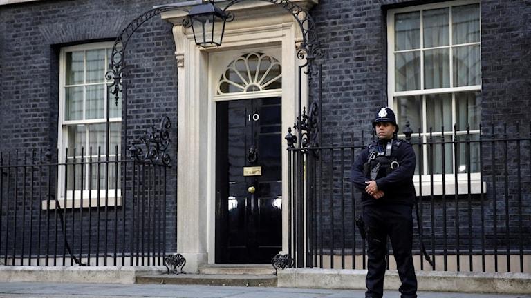 En polis står utanför ett hus.