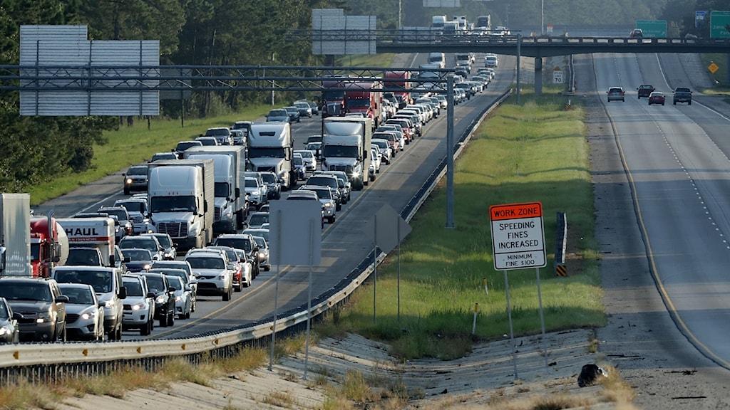 Motorväg full med bilar i ena riktningen och helt tom i andra.