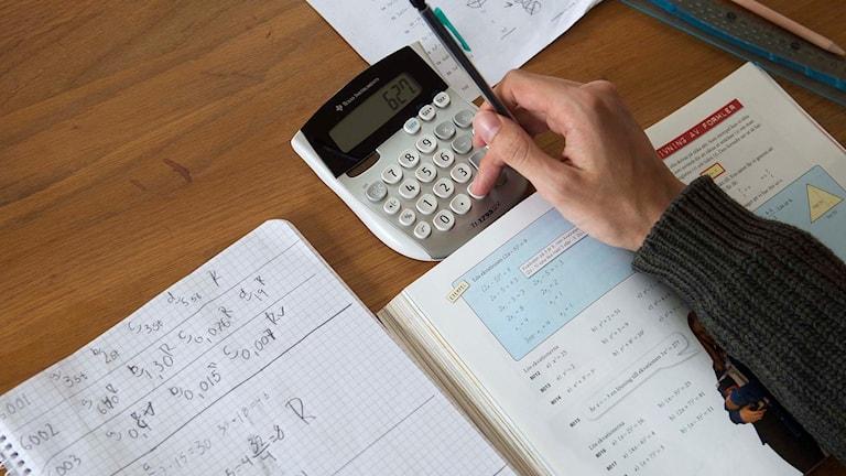 En person gör matematikuppgifter.