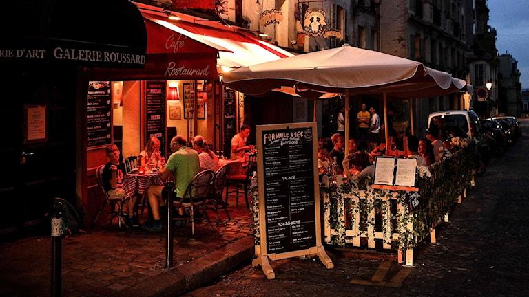 Människor sitter på en uteservering i Paris.