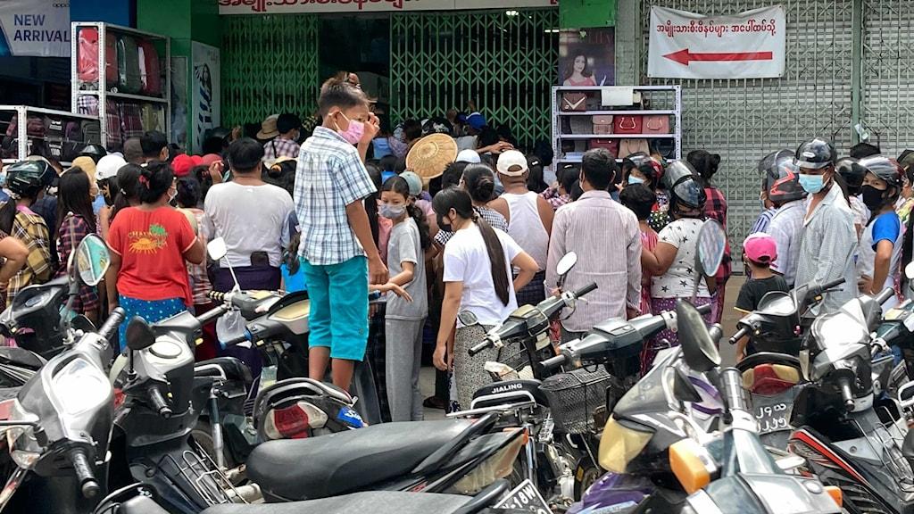 Litet barn i förgrunden av folkmassa framför butik.