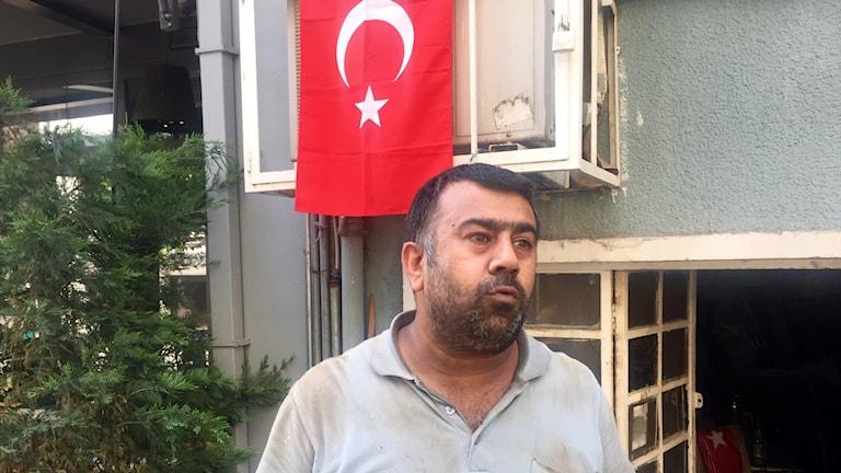 Man står framför turkisk flagga.