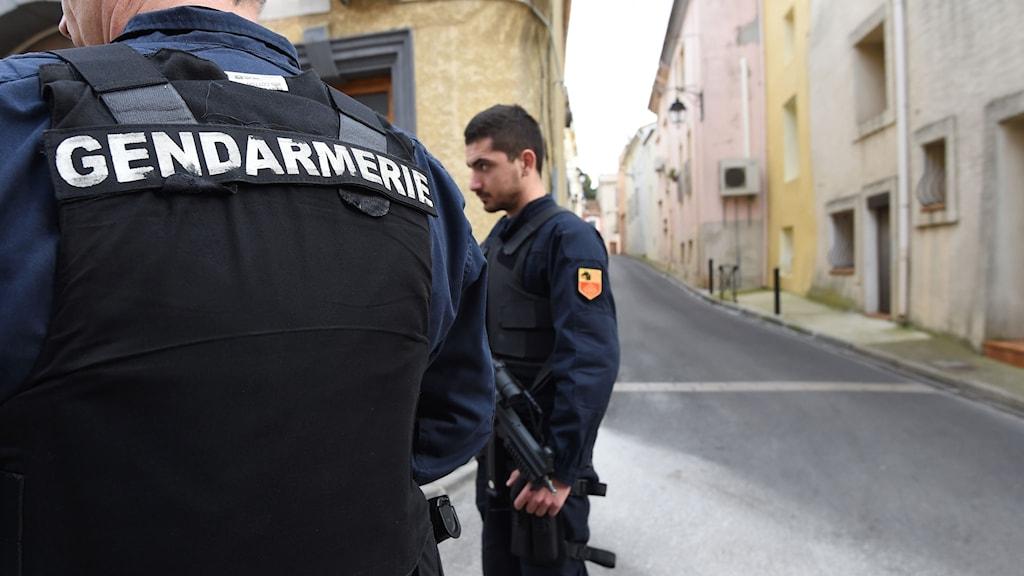 Beväpnade poliser står på en gata.