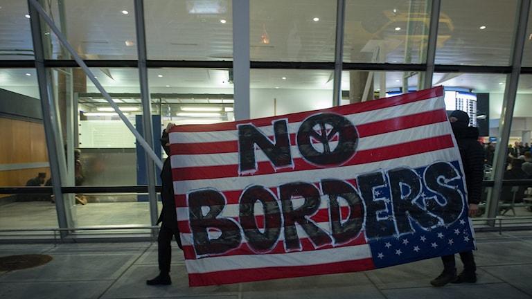 En amerikansk flagga med texten No Borders vid protest vid JFK-flygplatsen.