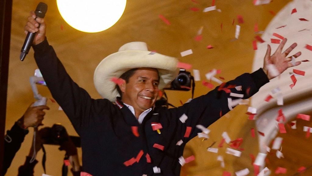 Man med stor hatt och uppsträckta armar på en scen under konfettiregn.