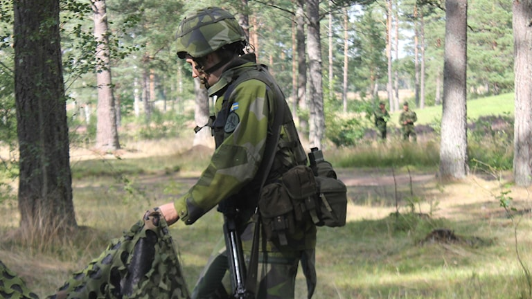 Värnpliktig i militäruniform lyfter en tältduk, i bakgrunden två uniformerade personer.
