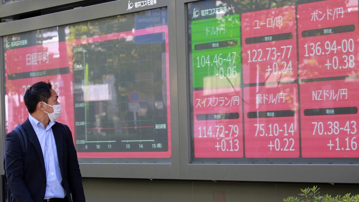 En man tittar på börsskärmar