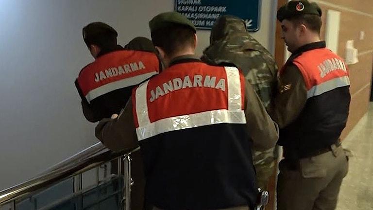 De två gripna grekiska soldaterna förs bort av turkiska paramilitära poliser.