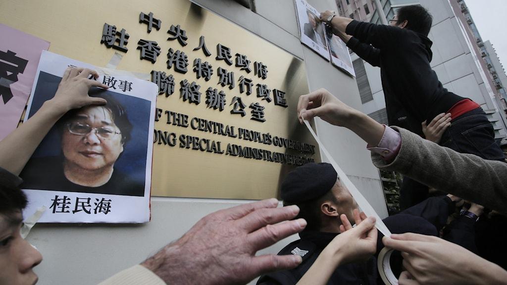 Demonstranter sätter upp affischer på saknade personer i Hongkong. På denna bild syns ett foto på den försvunne svensk-kinesiske förläggaren Gui Minhai.