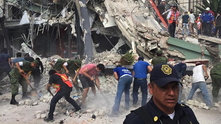 Ett hus har rasat ihop och människor gräver för att hitta personer som lever.