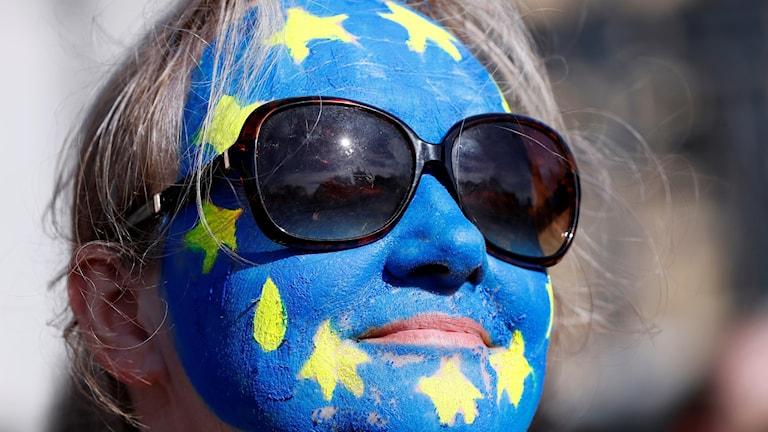 Kvinna med EU-flagga målad i ansiktet.