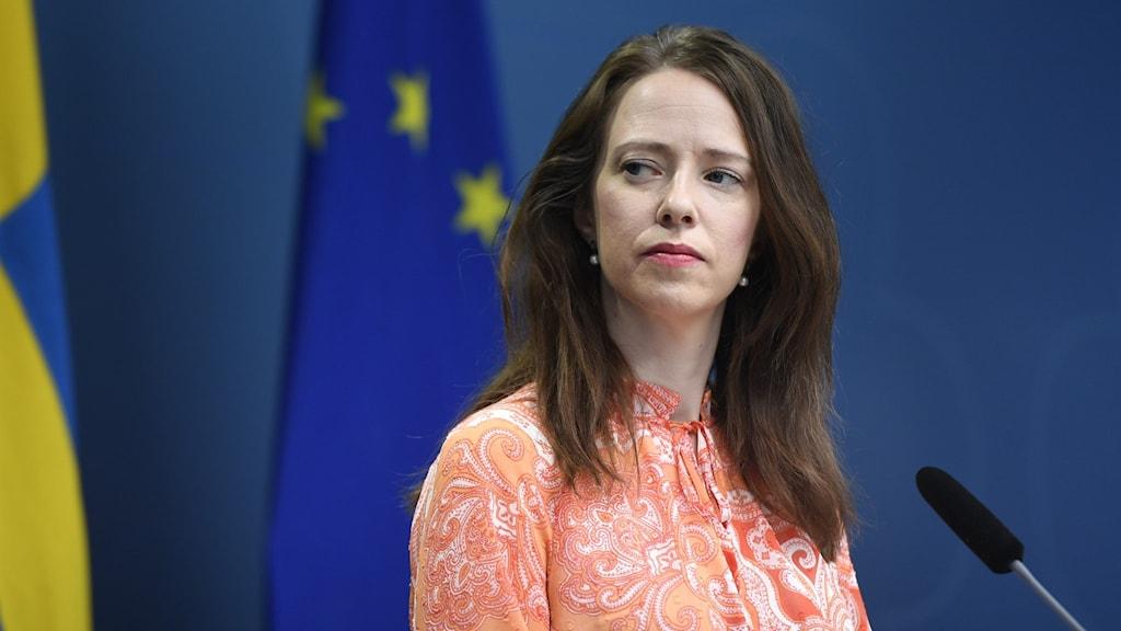 Bild på finansmarknadsminister Åsa Lindhagen framför en svensk och en EU-flagga.