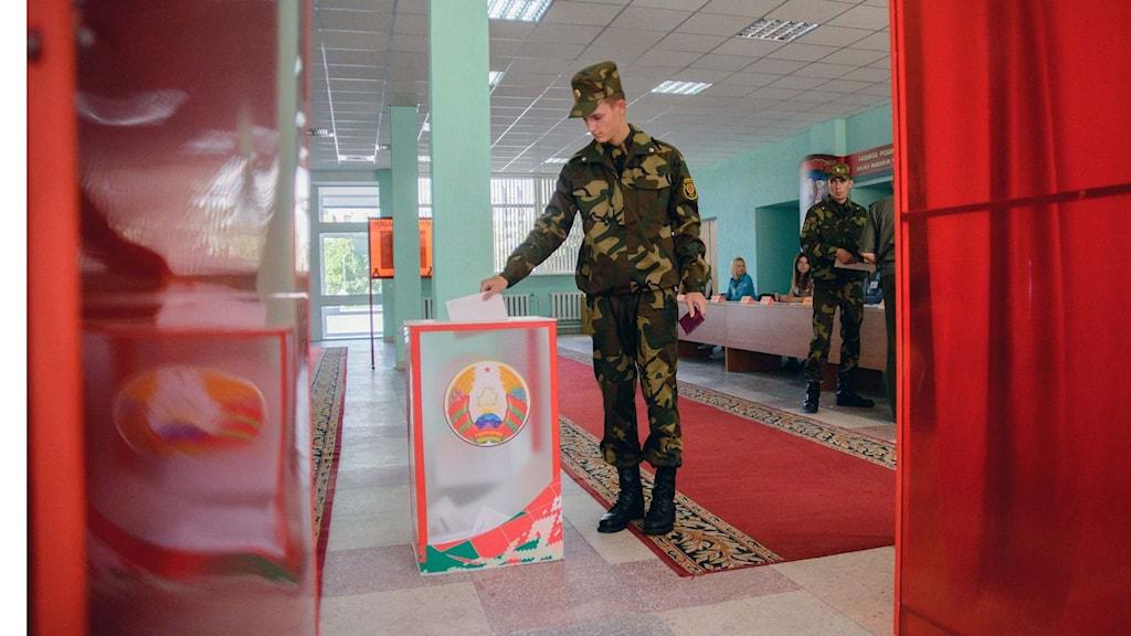 En soldat förtidsröstar i en vallokal i Minsk.