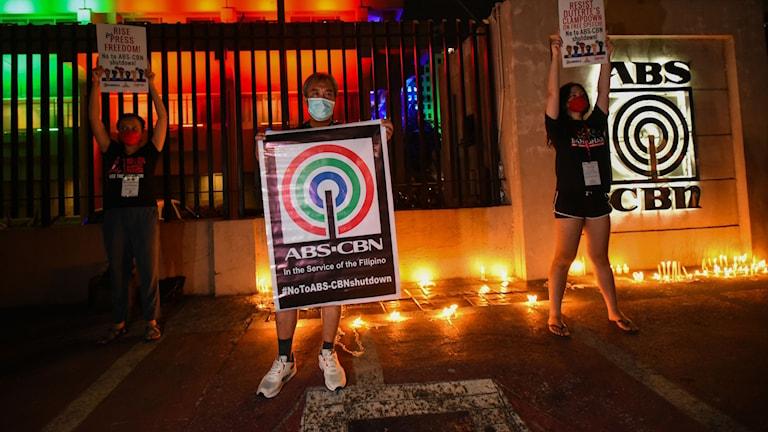 demonstranter tände ljus och stod med plakat utanför ABS CBN:s kontor.