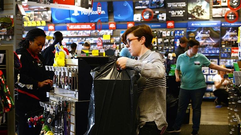 Arkivbild. I december försvann 20 000 jobb inom handeln i USA. Ett butiksbiträde fraktar varor.