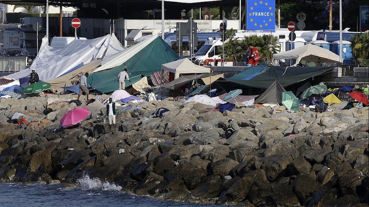Migranter och tält vid en strandkant.