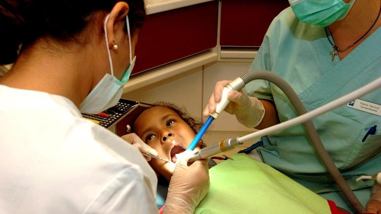 Ett barn blir undersökt av en tandläkare och en tandsköterska.
