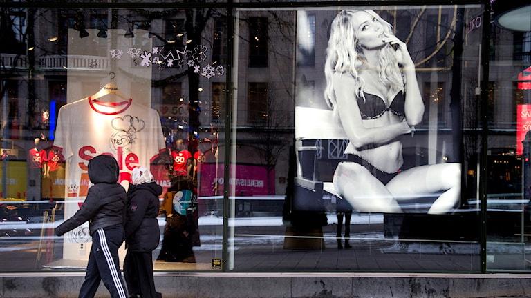 Privatpersoner går förbi skyltfönster med affisch med lättklädd kvinna