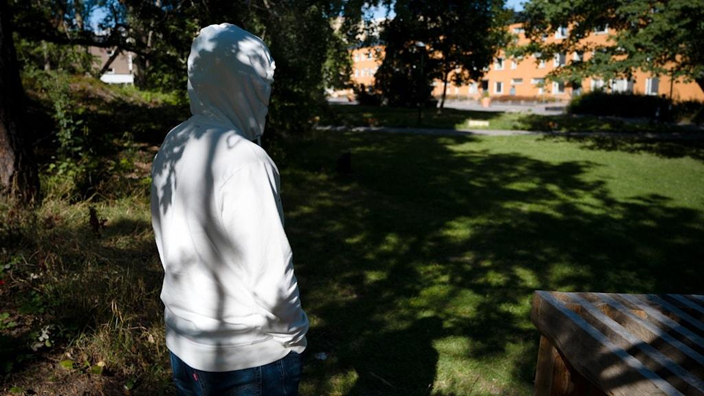 En person i vit huvtröja står framför några hyreshus.