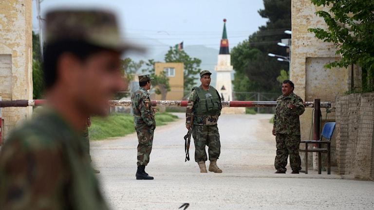 Soldat i förgrunden och soldater som vaktar ett militärläger.