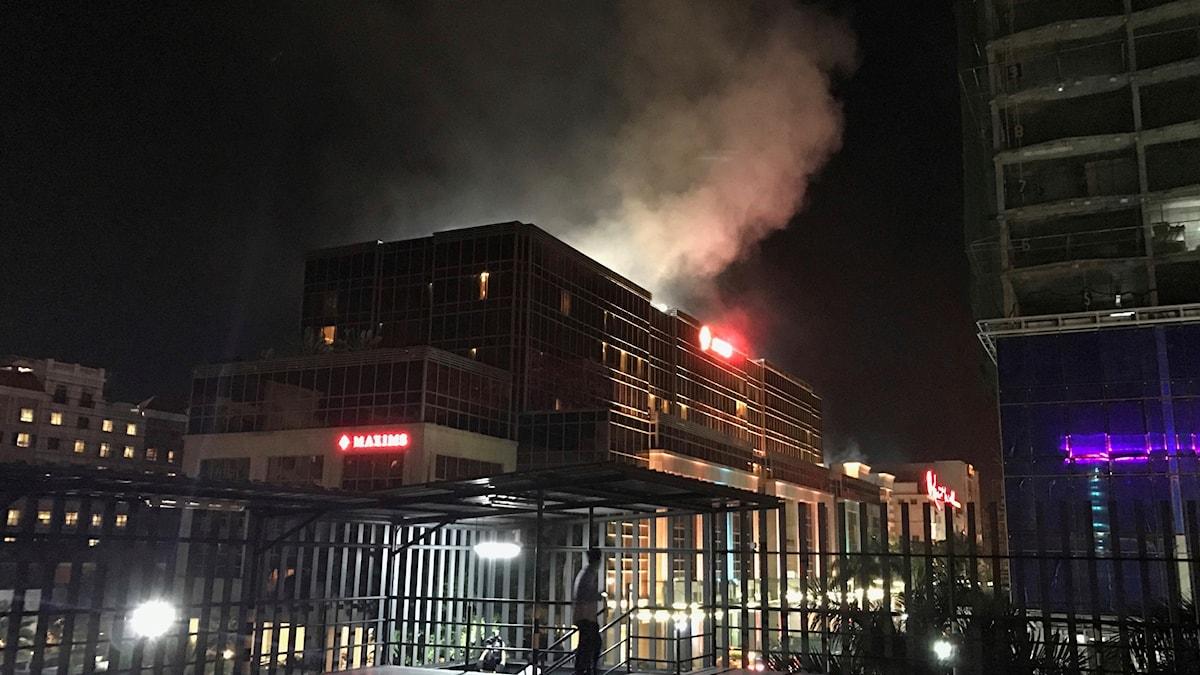 Rök stiger från den stora hotellanläggningen Resorts World Manila efter rapporter om skottlossning och explosion.