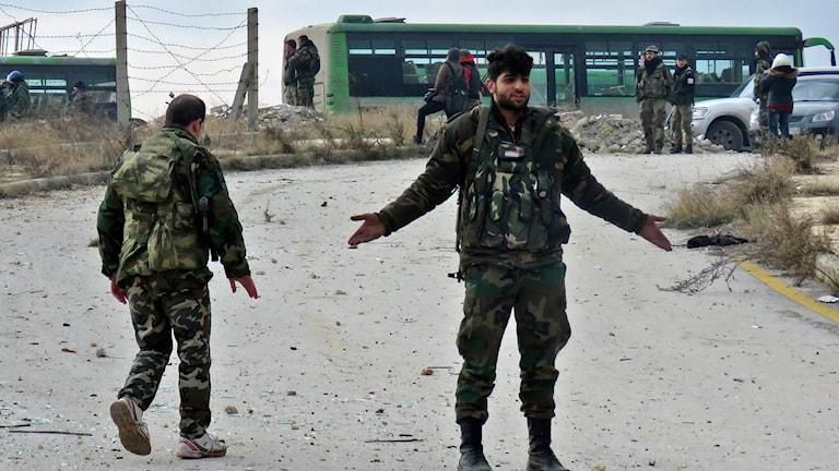 En syrisk soldat gestikulerar under evakueringen av Aleppo.