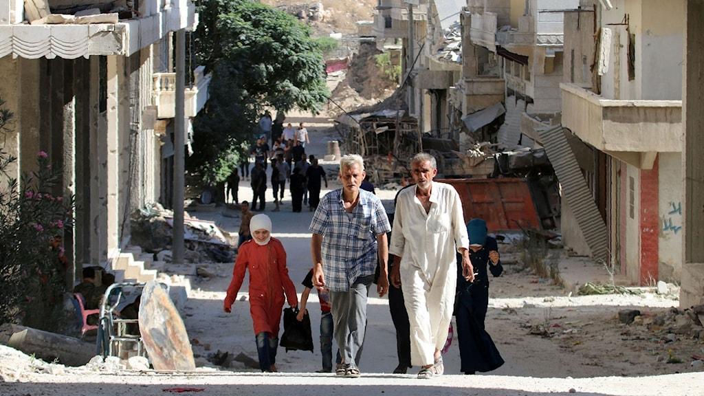 Människor går på en gata i utkanten av Aleppo i Syrien.