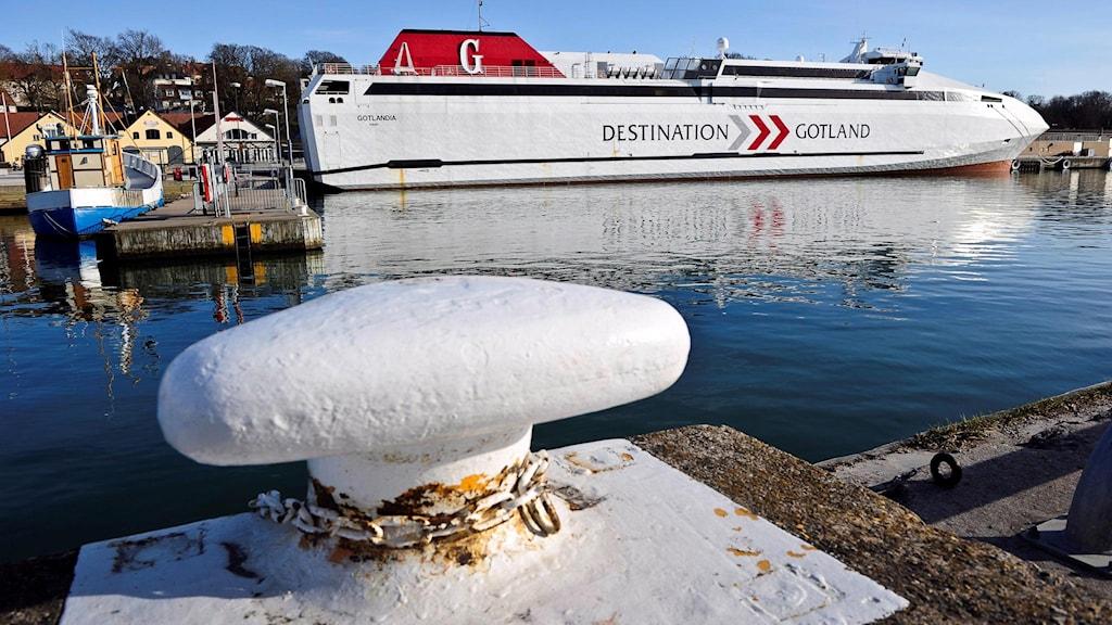 Hamnen i centrala Visby med en pollare i förgrunden och Gotlandsfärjan, Destination Gotland, i bakgrunden.