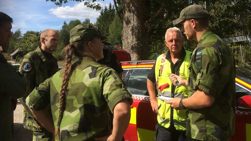 En grupp militärklädda personer och en räddningsledare i neongul väst samtalar. I bakgrunden syns en bil från räddningstjänsten.