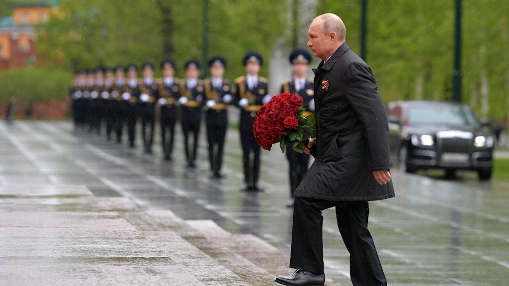 Putin bär en bukett med rosor.