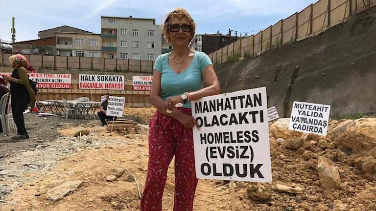 Det skulle bli som på Manhattan - men i stället blev vi hemlösa, står det på skylten som Zeynep Duzgunoglu står vid. Här skulle hennes färdiga hus stått.