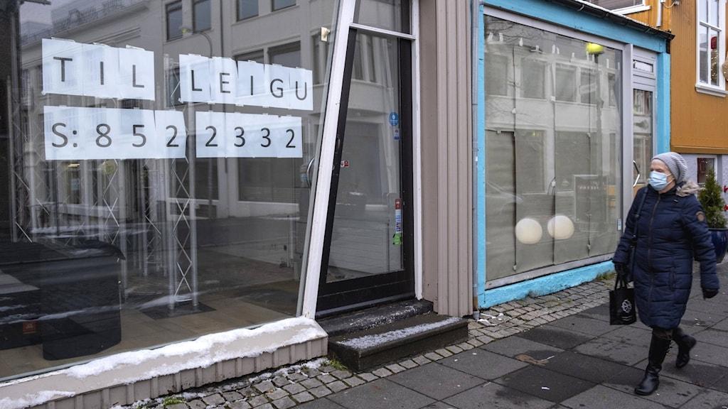 En kvinna utanför en tom butik i reykavik.