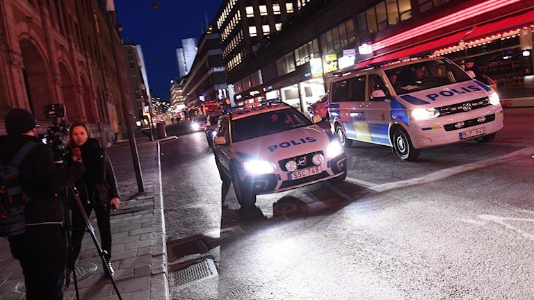 Två polisfordon på gata på kvällen.