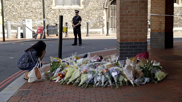 En kvinna lämnar en blomsterbukett vid platsen för knivdådet i Reading.