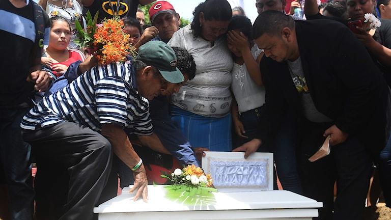 Människor sörjer vid begravningen av den dödade bebisen