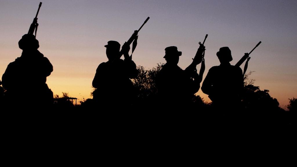 beväpnade män i solnedgång