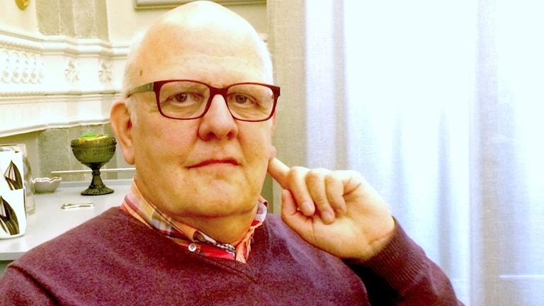 Fotot visar Sture Bergwall i röd tröja, glasögon och vitt mycket kort hår.