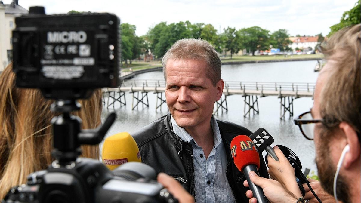 Foto av Kaj Linna utomhus omgiven av fotografer och reportrar.