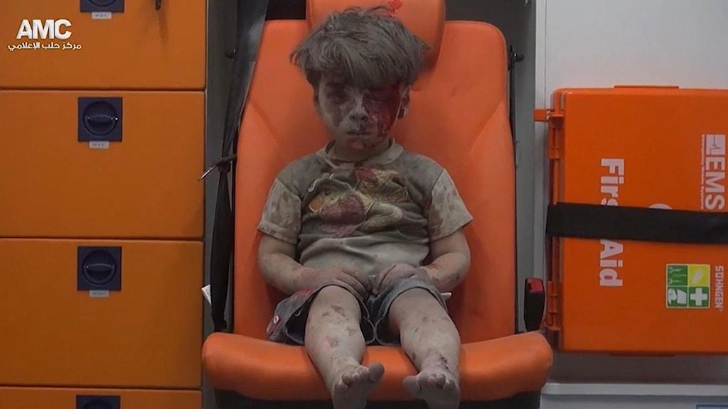 En pojke täckt av damm och med blod i ansiktet sitter i en ambulans efter att ha blivit räddad efter en bombattack i Aleppo.